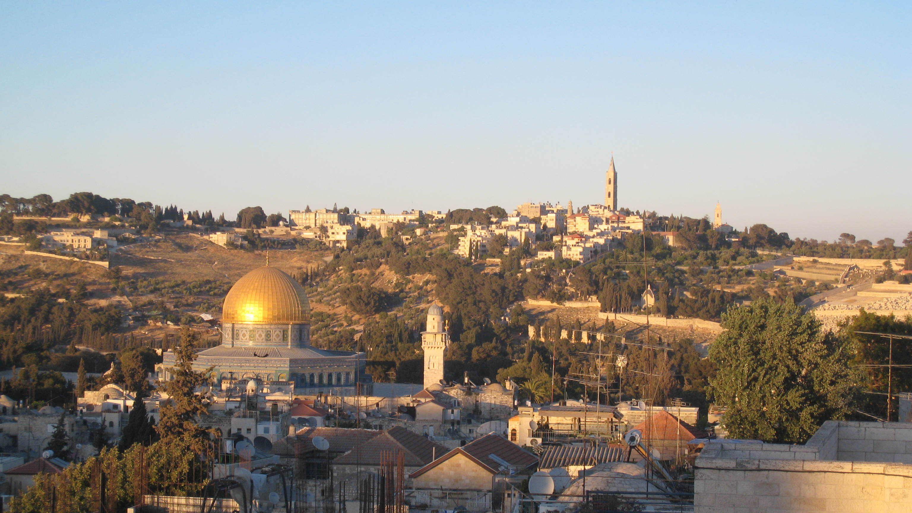 Above pieces of jerusalem s skyline from the roof deck at sunrise